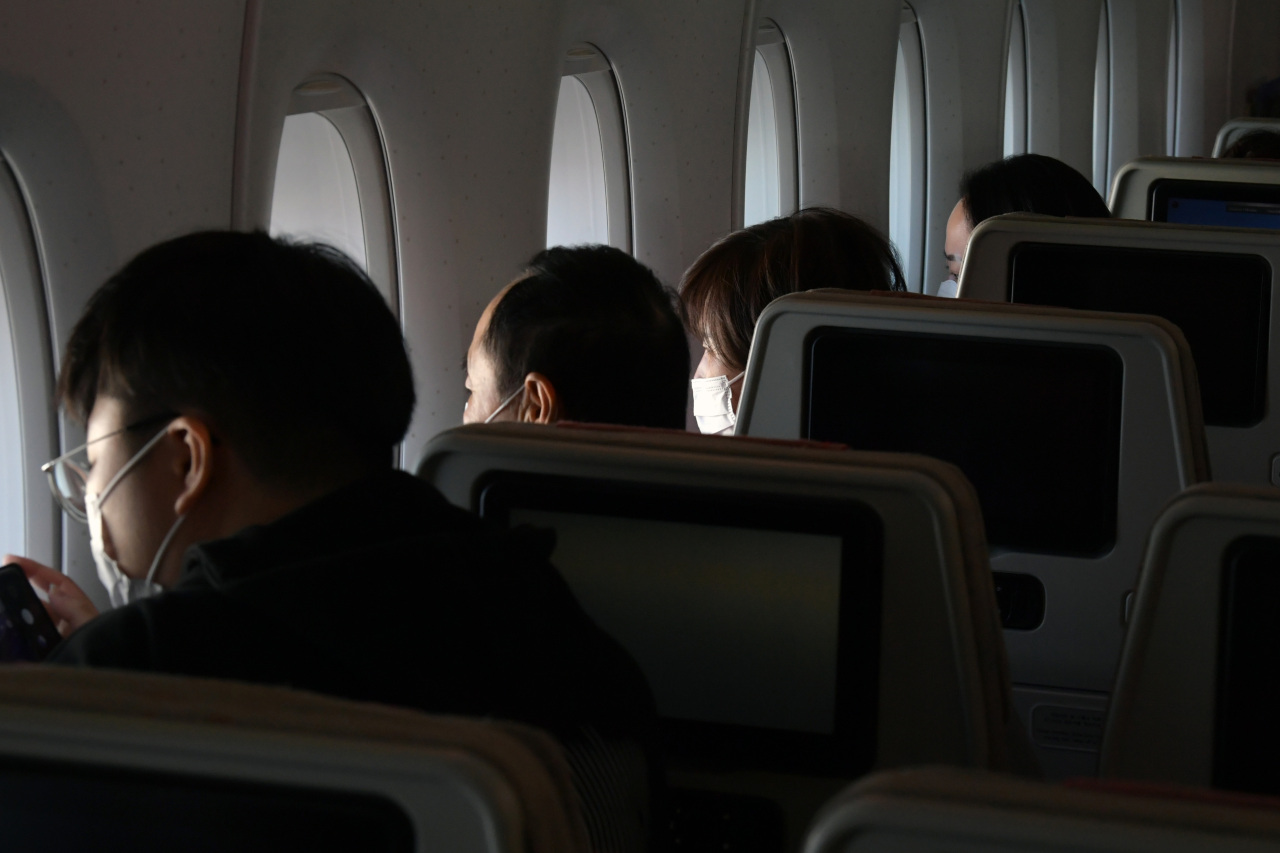 Passengers stare outside the windows in a sightseeing program offered by Asiana Airlines, in this photo taken on Oct. 24. (Yonhap)