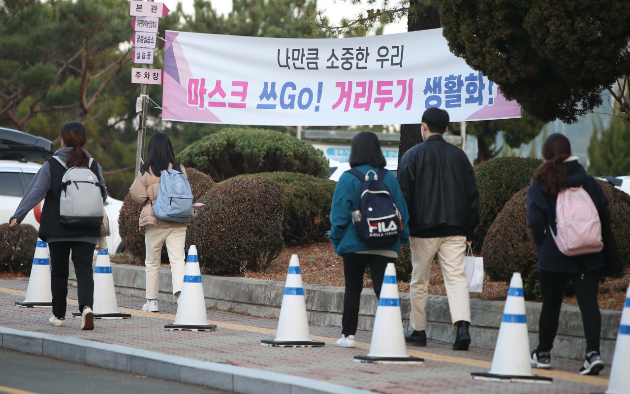A placard calls on people to wear masks and keep social distancing measures. (Yonhap)