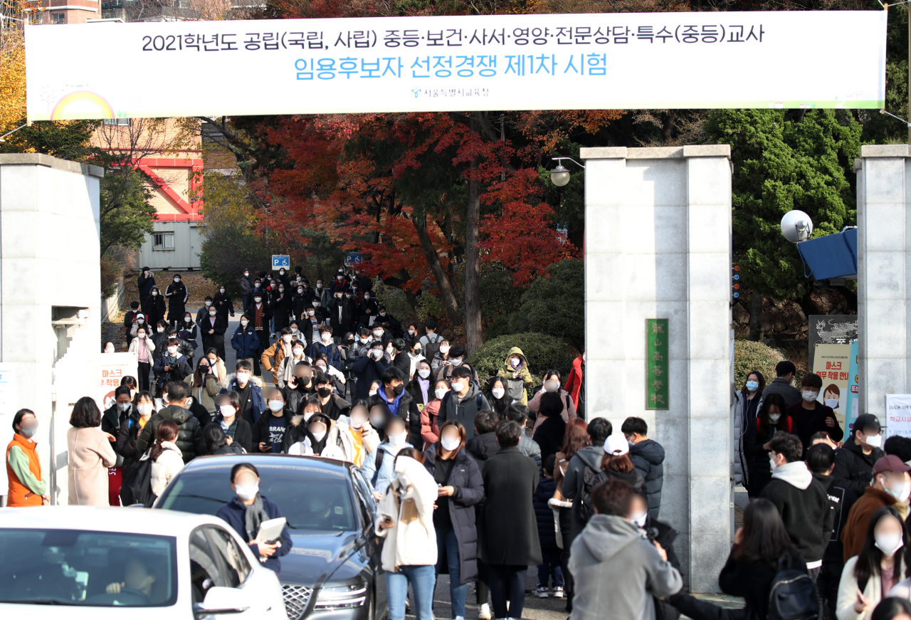 People walk out from a school in Seoul after taking the state-run teacher employment examination on Saturday. (Yonhap)