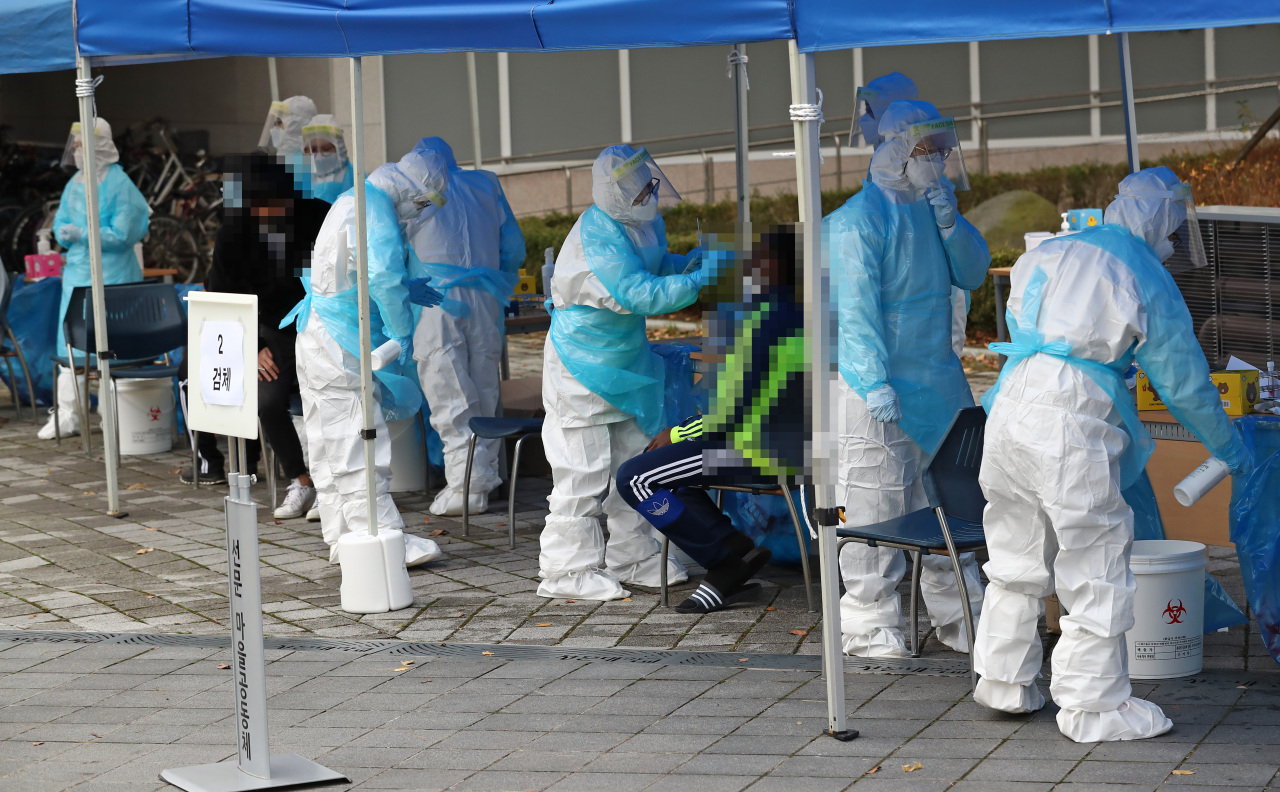 Health workers clad in protective gear speak with citizens at a makeshift virus testing clinic in Seoul on Friday. (Yonhap)