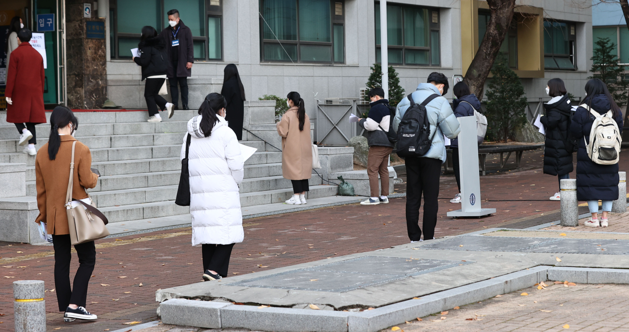 Early action applicants wait outside a Seoul university building for admissions interview Sunday. (Yonhap)