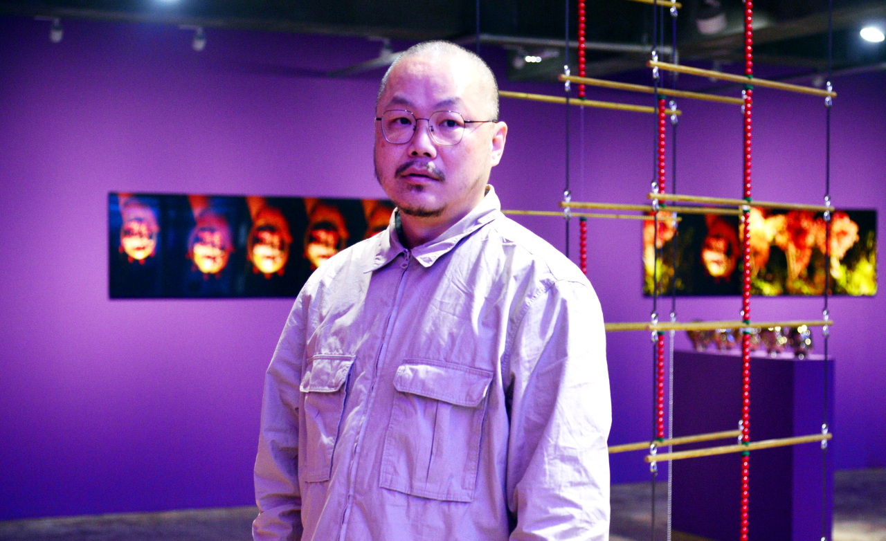 Artist Yangachi poses in front of his works at Barakat Contemporary (Park Hyun-koo/The Korea Herald)