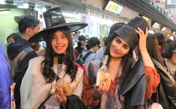Foreigners, wearing traditional costumes of the Joseon Dynasty (1392-1910), pose with Korean traditional cookies at Nammun Market in Suwon, Gyeonggi Province in May 2019. (Korea Tourism Organization)