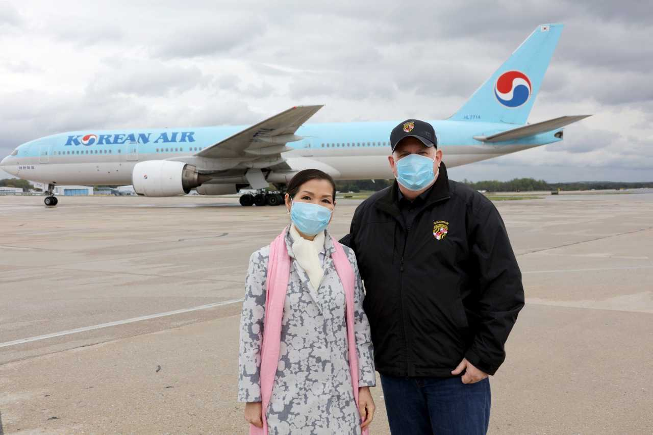 This photo, captured from the Twitter account of Maryland Gov. Larry Hogan, shows Hogan (R) and his Korean-American wife, Yumi Hogan, posing for a photo while welcoming the arrival of kits for 500,000 coronavirus tests at Baltimore-Washington International Thurgood Marshall Airport in the eastern United States on April 18. (Twitter account of Maryland Gov. Larry Hogan)