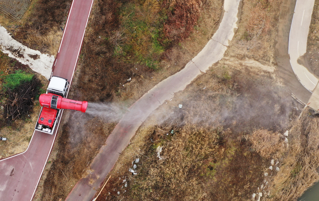 A truck sprays disinfectant at a wild bird habitat in Icheon, south of Seoul, last Friday. (Yonhap)