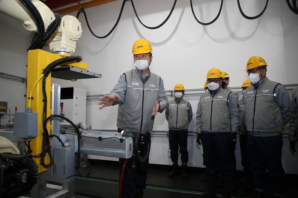 Officials from Daewoo Shipbuilding & Marine Engineering Co. look at an AI-based welding quality monitoring robot in Okpo, Geoje Island, about 400 kilometers south of Seoul. (Daewoo Shipbuilding & Marine Engineering Co.)
