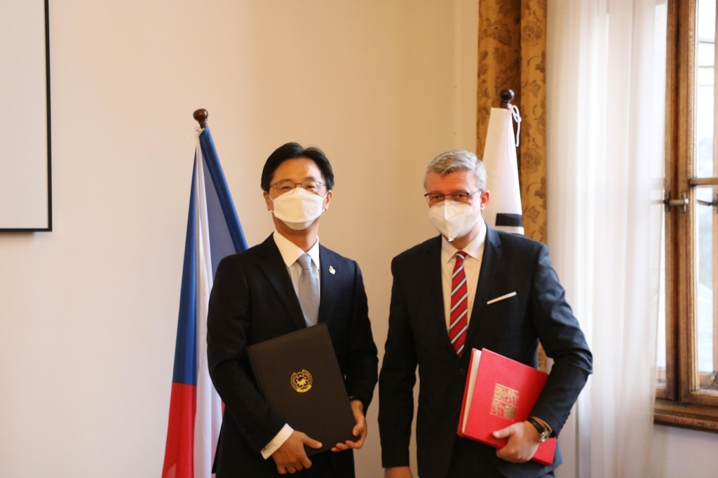 South Korean Ambassador to Prague Kim Tae-jin (L) poses for a photo with Czech Transport Minister Karel Havlicek after signing the amended air services agreement in Prague on Tuesday. (Ministry of Foreign Affairs)