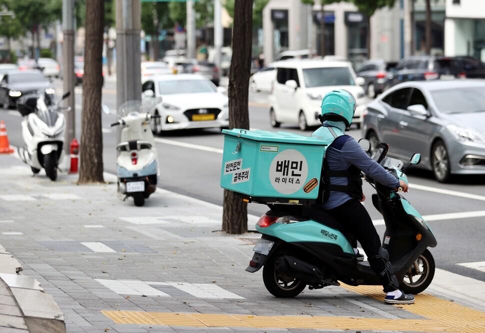 A Baemin delivery man rides a motorcycle. (Yonhap)