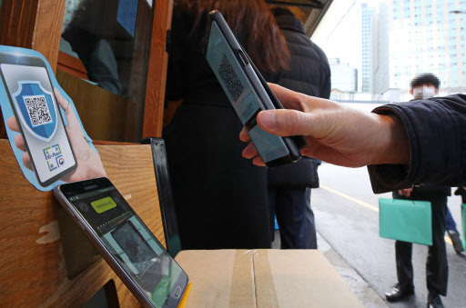 A man uses a QR check-in system before entering a restaurant in Seoul (Yonhap)