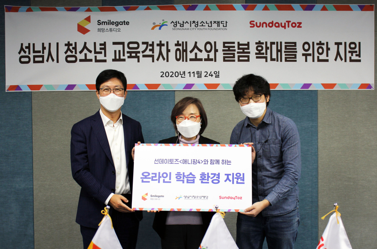 From left: Smilegate President Yang Dong-ki, Seongnam City Youth Foundation CEO Jin Mi-seok and SundayToz producer Lee Hyun-woo pose for a photo at a donation ceremony in an auditorium at the Seongnam City Youth Foundation on Tuesday. (Smilegate)