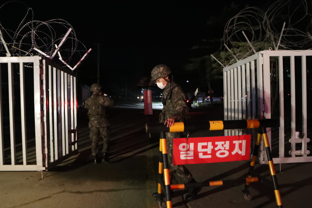 Soldiers close the front gate of an Army boot camp in the northern county of Yeoncheon on Wednesday, after 60 newly enlisted soldiers tested positive for the new coronavirus. (Yonhap)