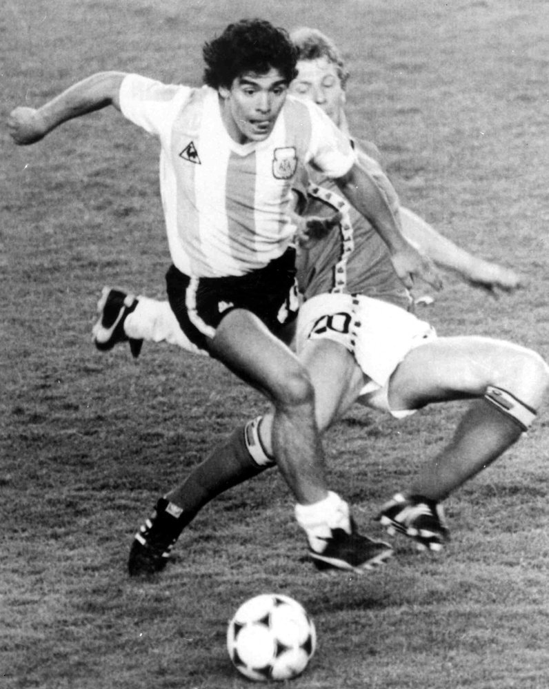In this June 13, 1982 file photo, Argentina's Diego Maradona, front, is attacked by Belgium's Guy Vandermissen during the opening game of the Soccer World Cup in Barcelona, Spain. The Argentine soccer great who was among the best players ever and who led his country to the 1986 World Cup title before later struggling with cocaine use and obesity, died from a heart attack on Wednesday, at home in Buenos Aires. He was 60.(AP-Yonhap)