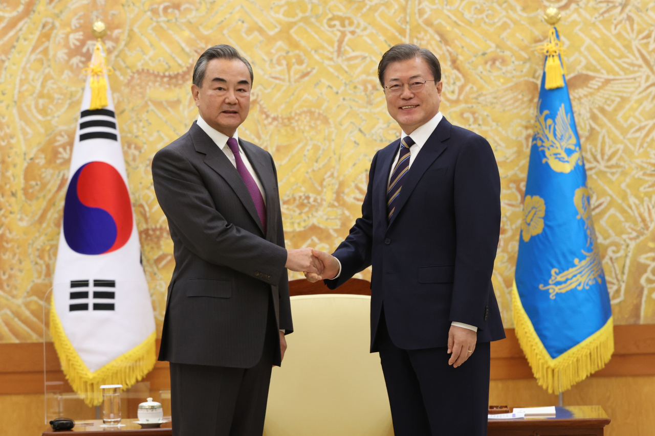 President Moon Jae-in and Chinese Foreign Minister Wang Yi (left) pose for a photograph at Cheong Wa Dae on Thursday. (Yonhap)