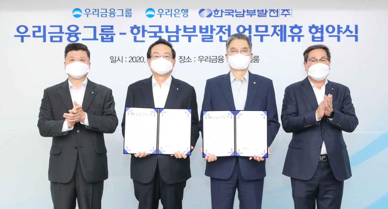 (From left) Woori Bank CEO Kwon Kwang-seok, Woori Financial Group Chairman Sohn Tae-seung, Korea Southern Power Co. President and CEO Shin Jeong-shik and KSP Vice President Song Ki-in pose after establishing a working-level partnership to financially support the utility company's solar energy, hydrogen, and fuel cell projects on Nov. 13, in Seoul. (Woori Bank)