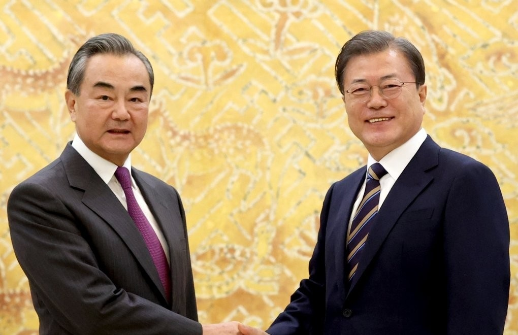 South Korean President Moon Jae-in (right) shakes hands with Chinese Foreign Minister Wang Yi at Cheong Wa Dae in Seoul on Thursday. (Yonhap)