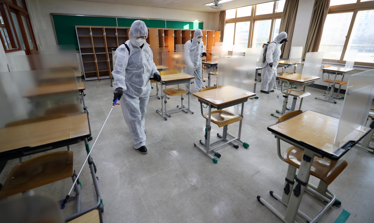 Health workers disinfect a classroom at a school in Daegu on Thursday, one week before the national college entrance exam. (Yonhap)