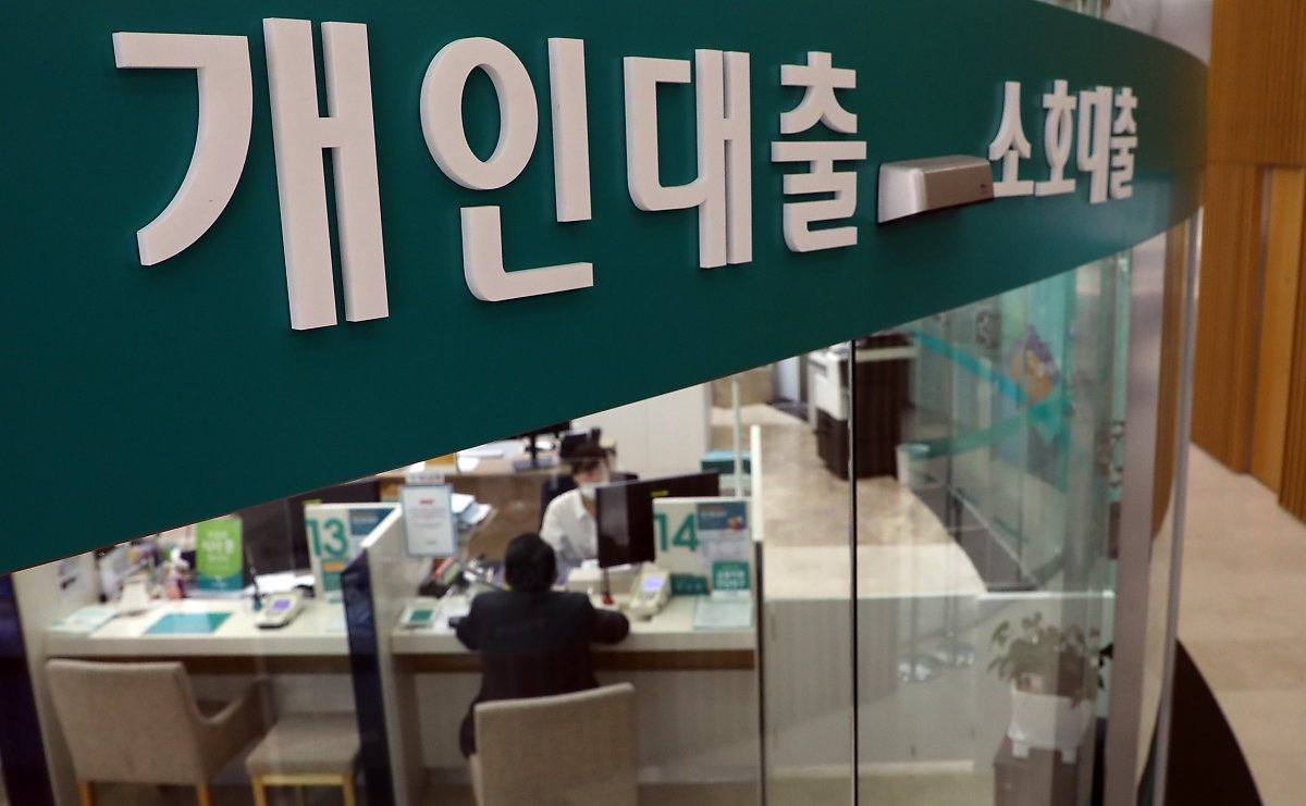 A bank official explains a loan product to a visiting customer. (Yonhap)