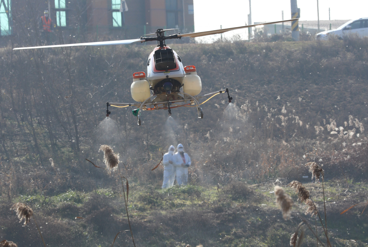 Officials of South Korea's agriculture ministry steer an unmanned chopper last Thursday, to disinfect wintering sites for migratory birds in Cheongju, 137 kilometers south of Seoul, as part of efforts to curb the spread of bird flu. (Yonhap)