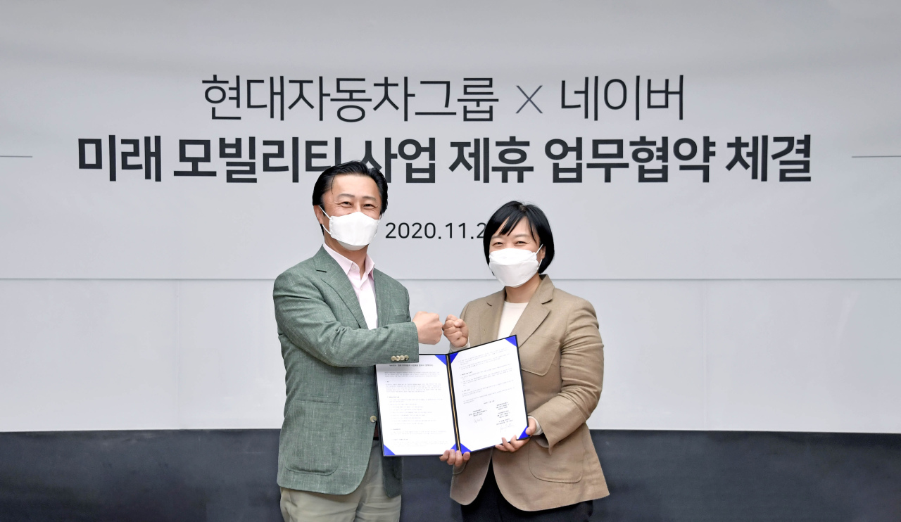 Chi Young-cho (left), executive vice president of Hyundai Motor Group's strategy and technology division, and Naver CEO Han Seong-sook pose during a signing ceremony at Naver's Green Factory in Seongnam, Gyeonggi Province, Friday. (Hyundai Motor Group)