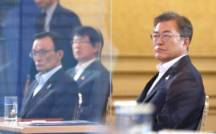 """President Moon Jae-in (right) listens to a policy briefing from Finance Minister Hong Nam-ki at Cheong Wa Dae on July 14, 2020, where Moon unveiled a road map to create 890,000 jobs by 2022 using 68 trillion won ($61.5 billion). The administration called it a part of """"the Korean New Deal."""" (Yonhap)"""