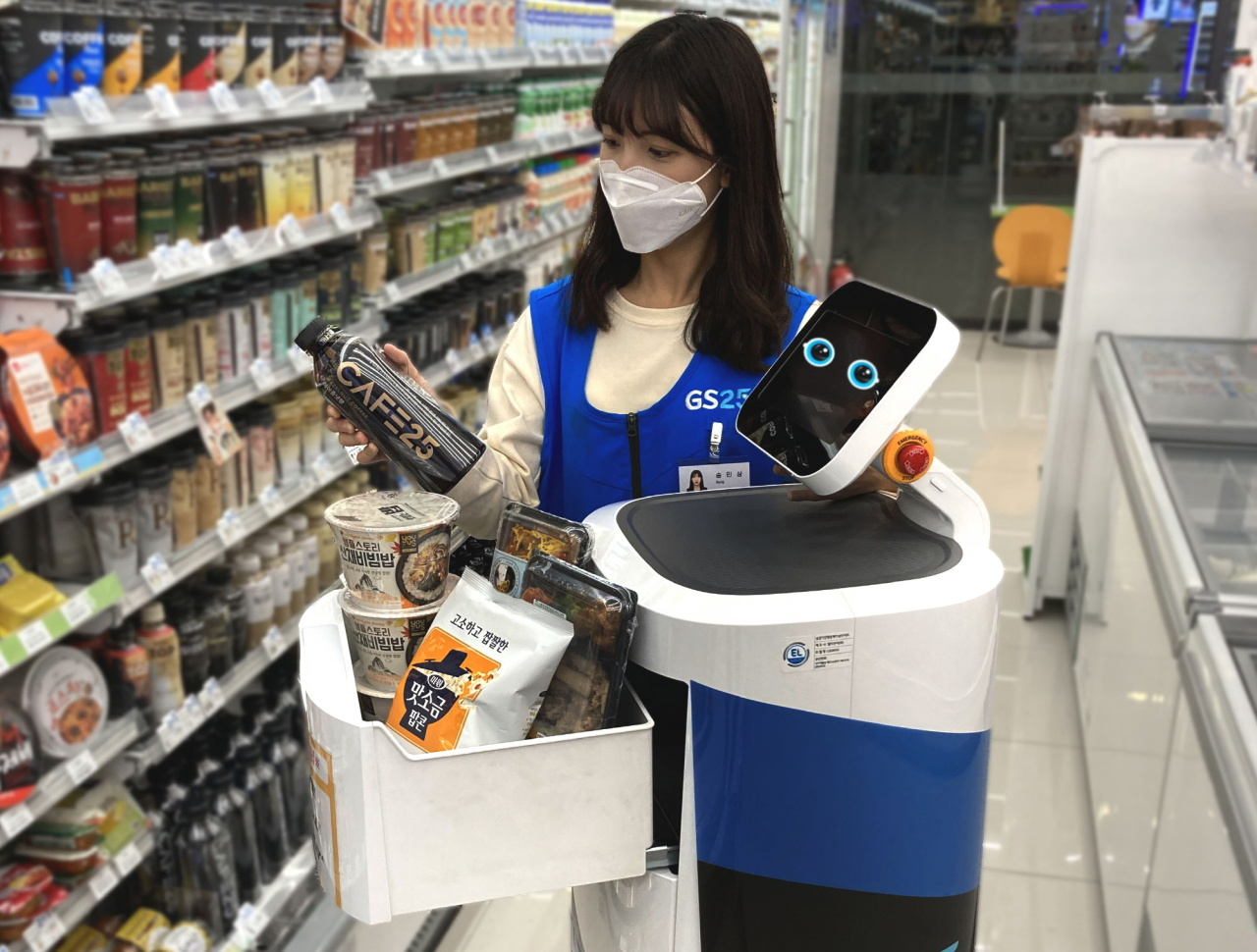 A GS25 convenience store employee moves items to a helper robot developed by LG Electronics.