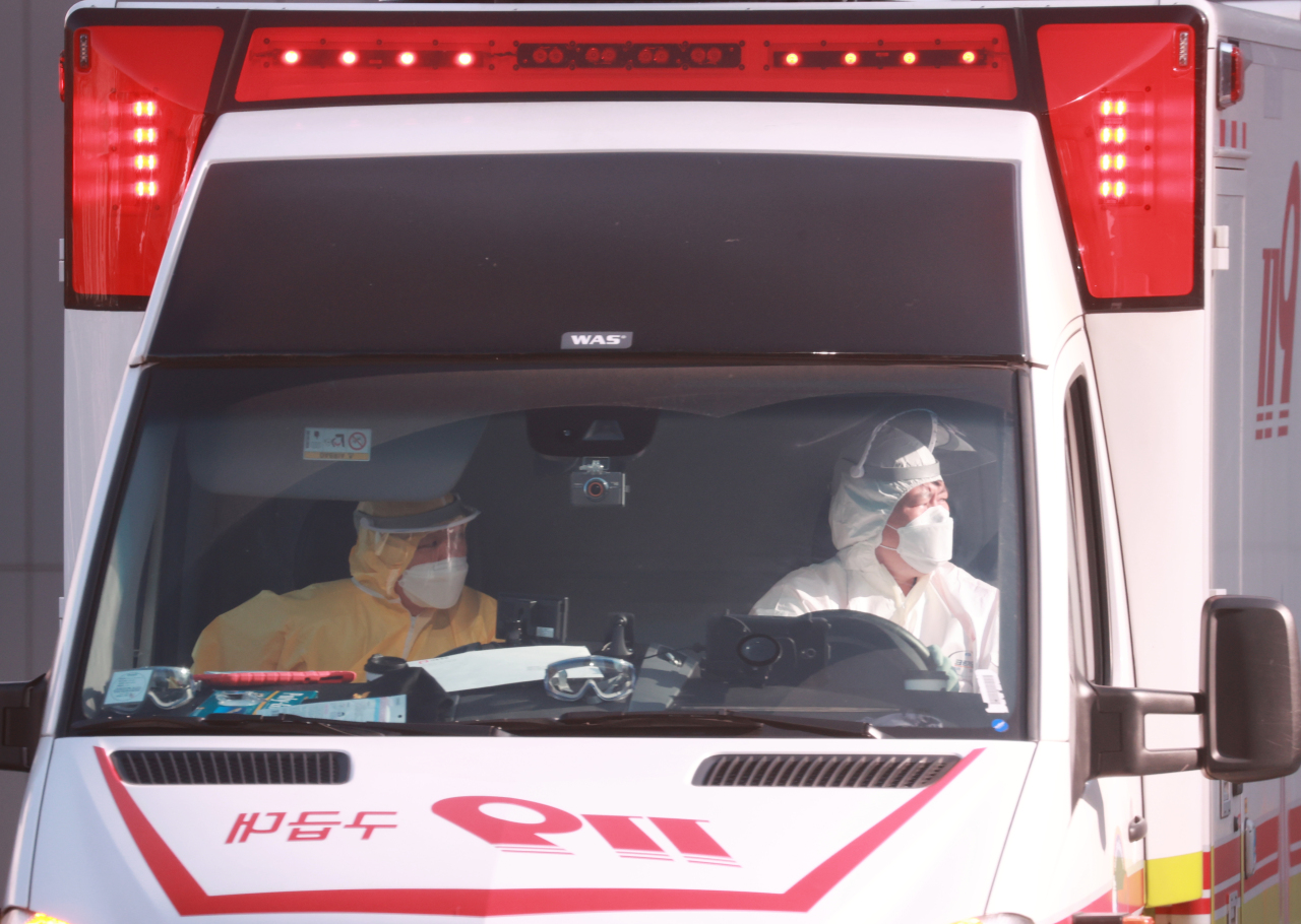 Rescue workers clad in protective gear transport patients infected with the new coronavirus in an ambulance to a negative-pressure ward at the National Medical Center in Seoul on Monday. (Yonhap)