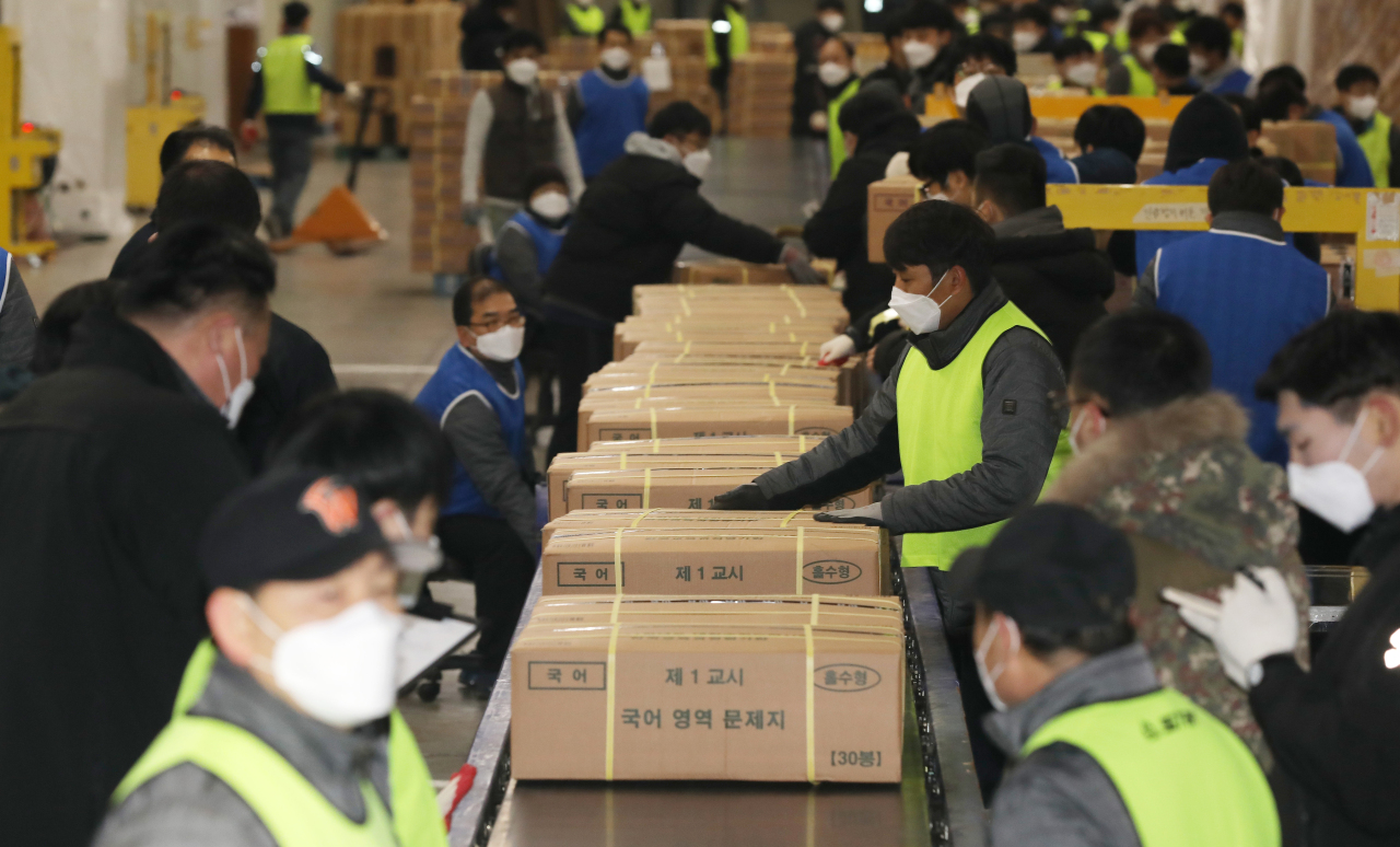 Officials prepare boxes containing test papers at a printing factory in Sejong on Monday to be delivered to local test administration authorities for Thursday's national college entrance exam. (Yonhap)