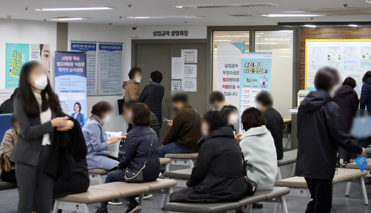 A group of people are on standby in front of a briefing room for unemployment benefits at a regional office of the Employment and Welfare Plus Center in Seoul earlier this year. (Yonhap)