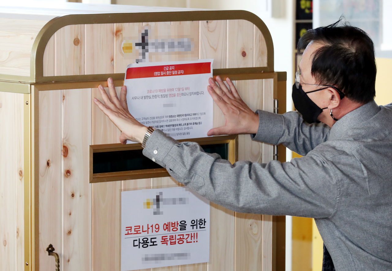 An official puts up a notice banning the use of sauna facilities at a public bath in Incheon, west of Seoul, on Monday, as the central government toughened social distancing rules until Dec. 7 amid the resurgence of the coronavirus. (Yonhap)