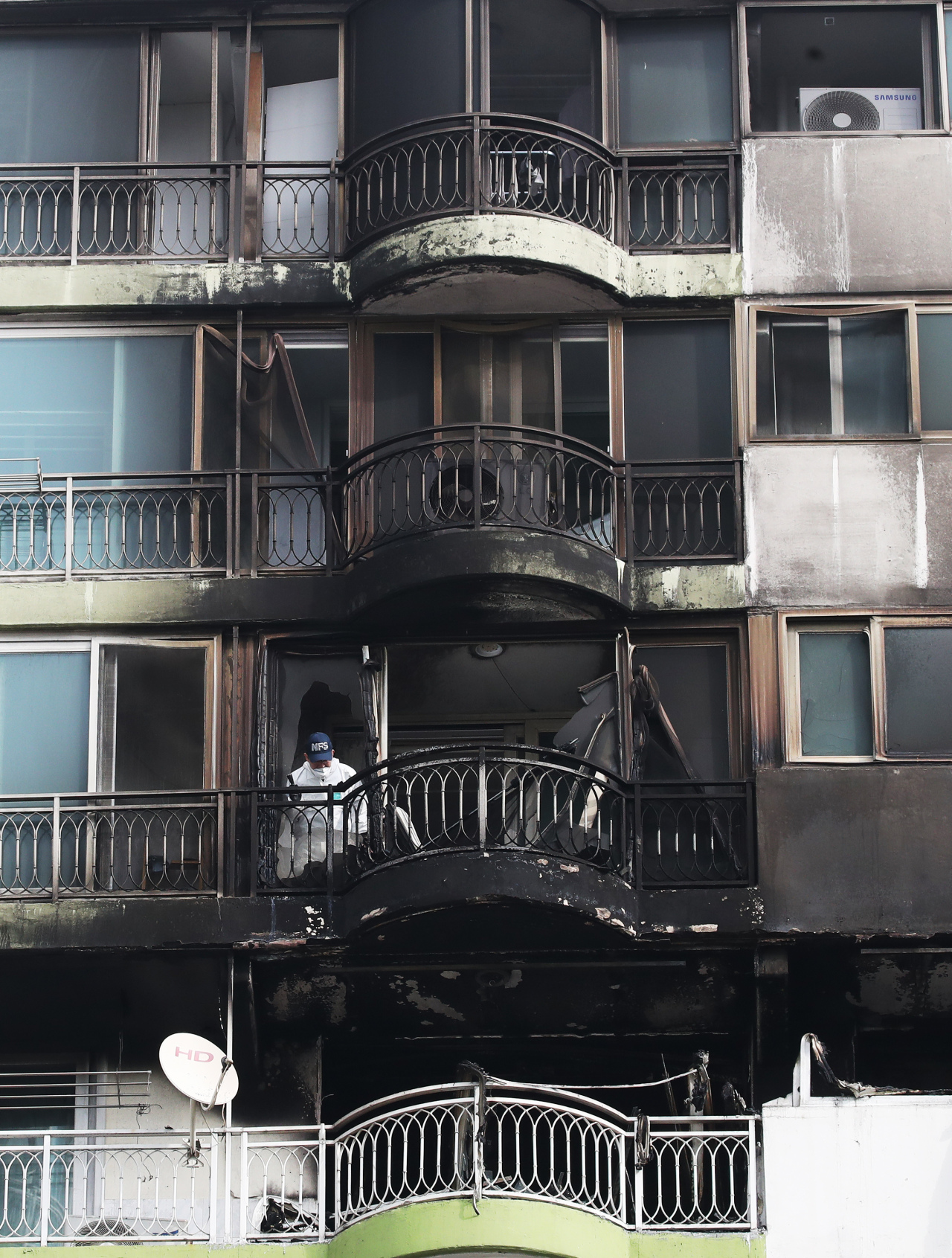 Forensic officials inspect a gutted apartment unit in Gunpo, Gyeonggi Province, on Wednesday. A fire there killed four and injured seven others Tuesday. (Yonhap)