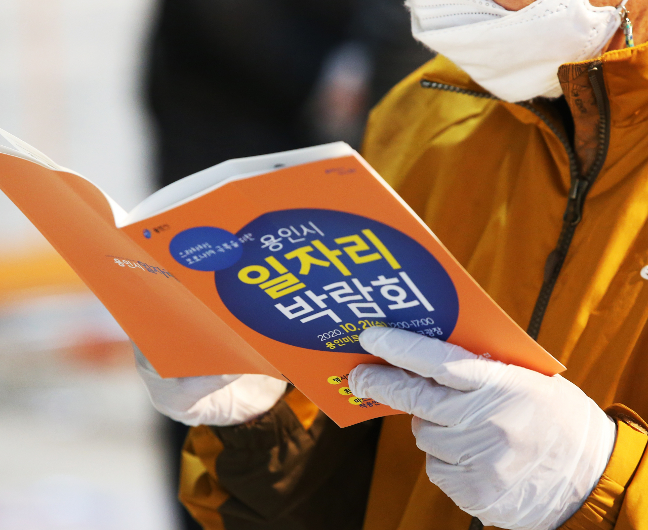 Wearing a mask and plastic gloves, a job seeker reads a pamphlet at a job fair in Yongin, just south of Seoul, on Oct. 21. (Yonhap)