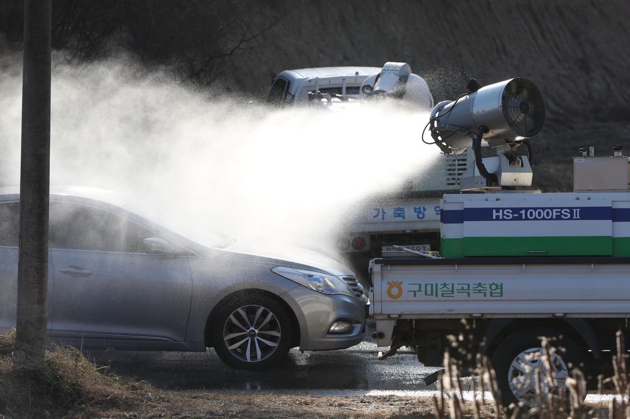 Agricultural officials disinfect an automobile near a farm located in Sangju, 270 km southeast of Seoul, on Wednesday. (Yonhap)