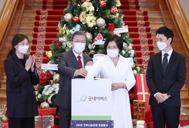 President Moon Jae-in (2nd from L) and first lady Kim Jung-sook (2nd from R) pose for photos as they make a personal donation to charity organization Good Neighbors at Cheong Wa Dae in Seoul on Friday. Moon invited representatives of 14 major charity organizations to Cheong Wa Dae to encourage them for their much-needed work in helping out the needy. (Yonhap)