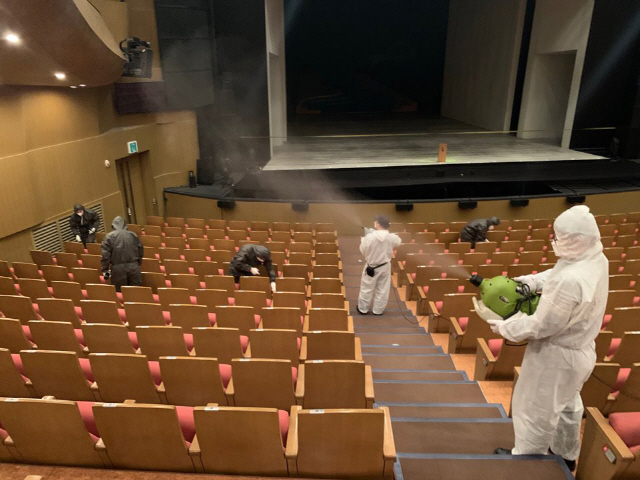Workers disinfect an auditorium at a performing art venue. (Yonhap)