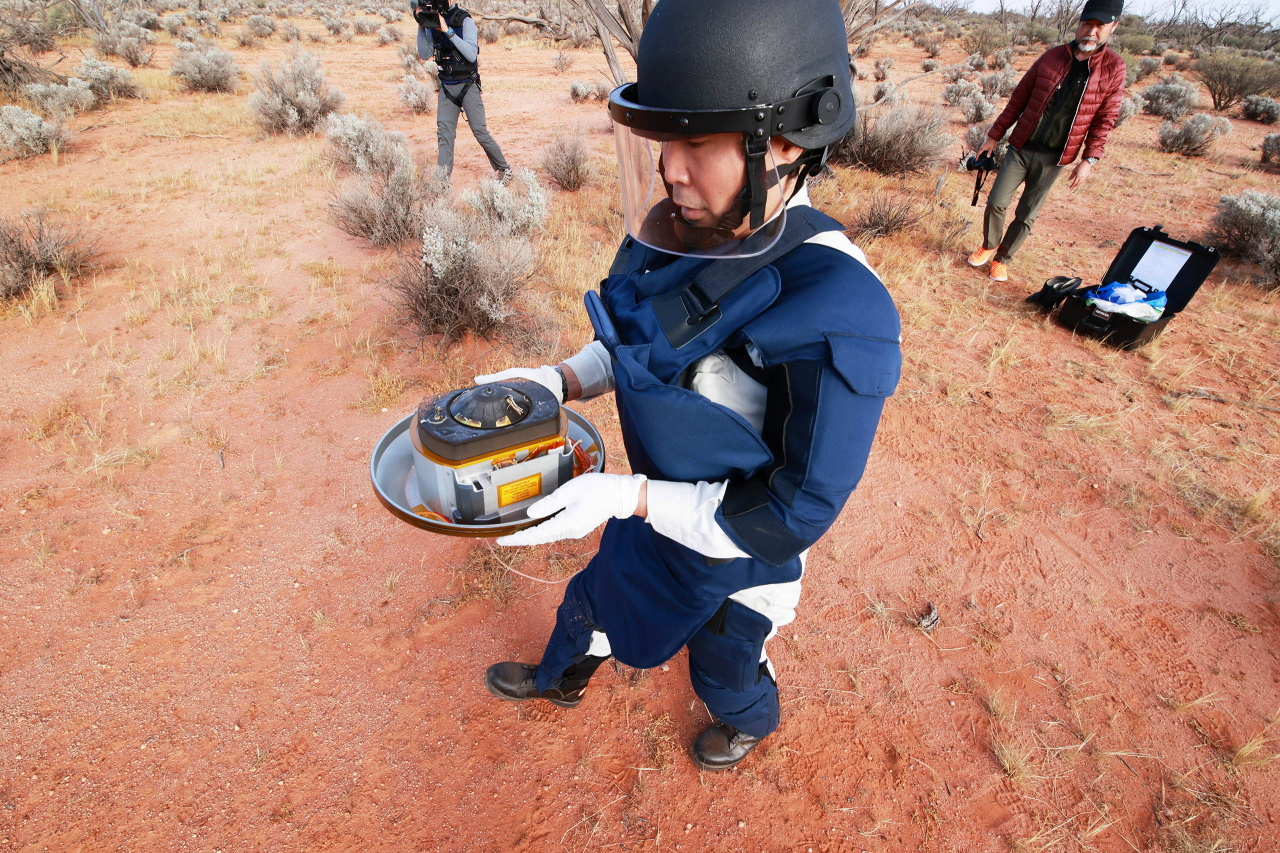 In this handout image from Japan Aerospace Exploration Agency (JAXA), a member of JAXA collects Hayabusa2's capsule carrying the first extensive samples of an asteroid after it landed in the Woomera restricted area, Australia, Sunday. (JAXA)