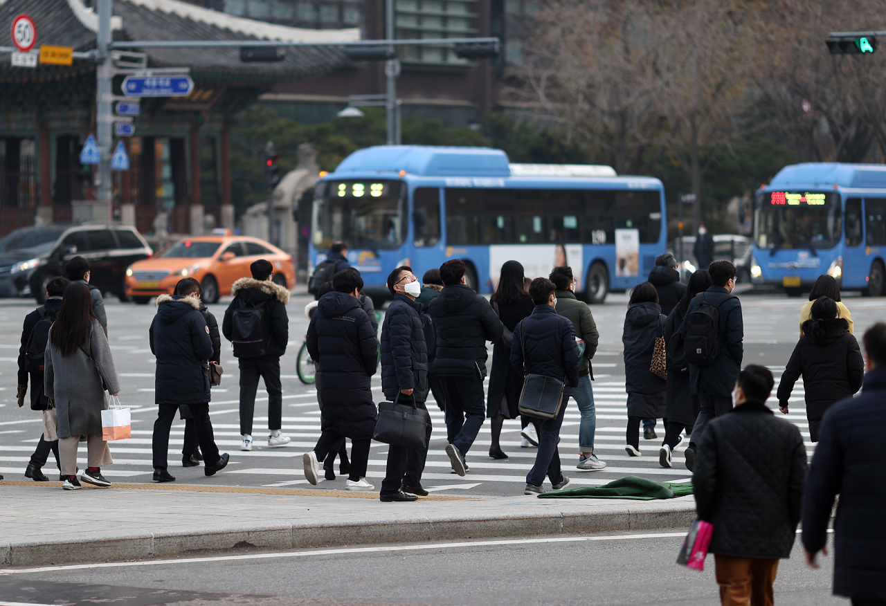 Citizens cross a street in Seoul on Monday, as the new virus cases stayed above 600 for the second consecutive day. (Yonhap)