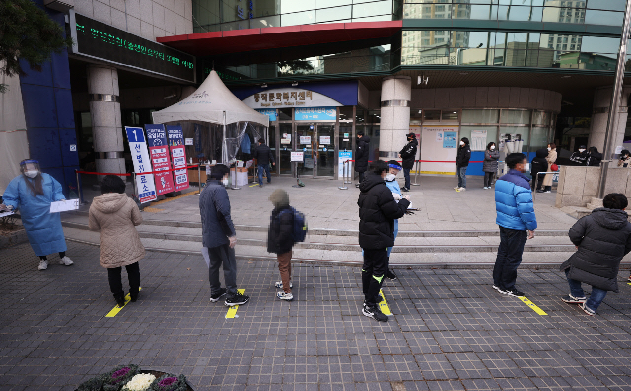People stand in a long line to take virus tests at a screening center in southwestern Seoul on Monday. (Yonhap)