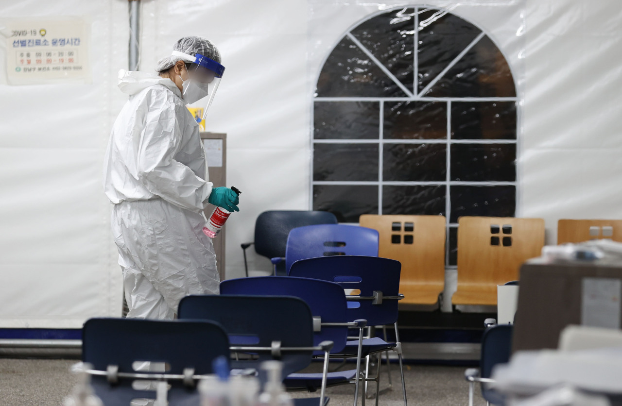 A medical worker sterilizes a screening station for COVID-19 in southern Seoul on Monday. (Yonhap)