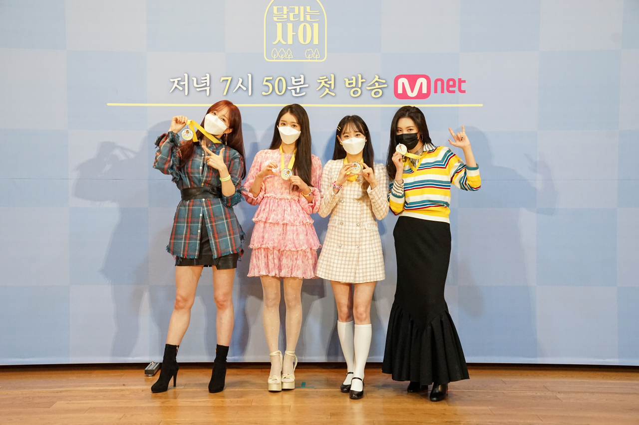 """(From left) K-pop idols Hani (EXID), YooA (Oh My Girl), Chuu (Loona) and Sunmi pose before an online press conference for Mnet's """"Running Girls"""" on Tuesday. (Mnet)"""