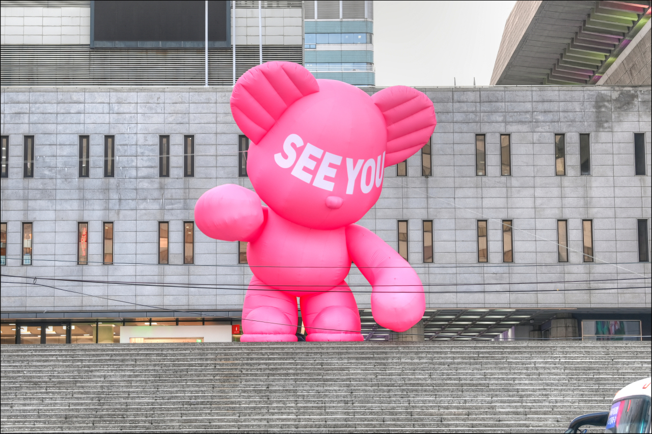 A newly installed edition of Hug Bear stands on a staircase at the Sejong Center for the Performing Arts in Gwanghwamun, central Seoul. The installation work is part of the Seoul City's Pink Light campaign, which supports the fight against the COVID-19 pandemic. (Sejong Center)
