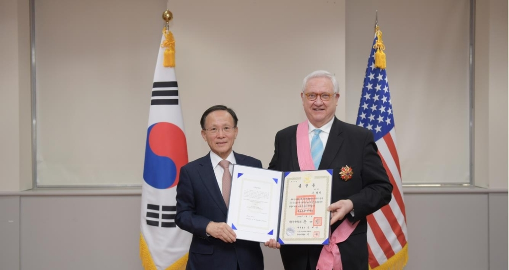 Ambassador Lee Soo-hyuck (L) and John Hamre, president of a US think tank, the Center for Strategic and International Studies, pose for a photo in a ceremony held on Tuesday in Washington. (South Korean Embassy in the United States)