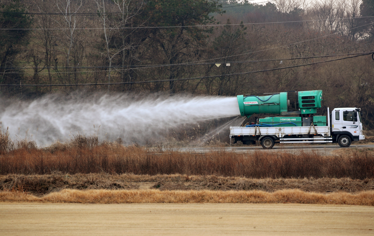 A truck sprays disinfectant near a duck farm in Janseong in South Jeolla Province last Friday, after outbreak of a highly pathogenic bird flu in the region. (Yonhap)