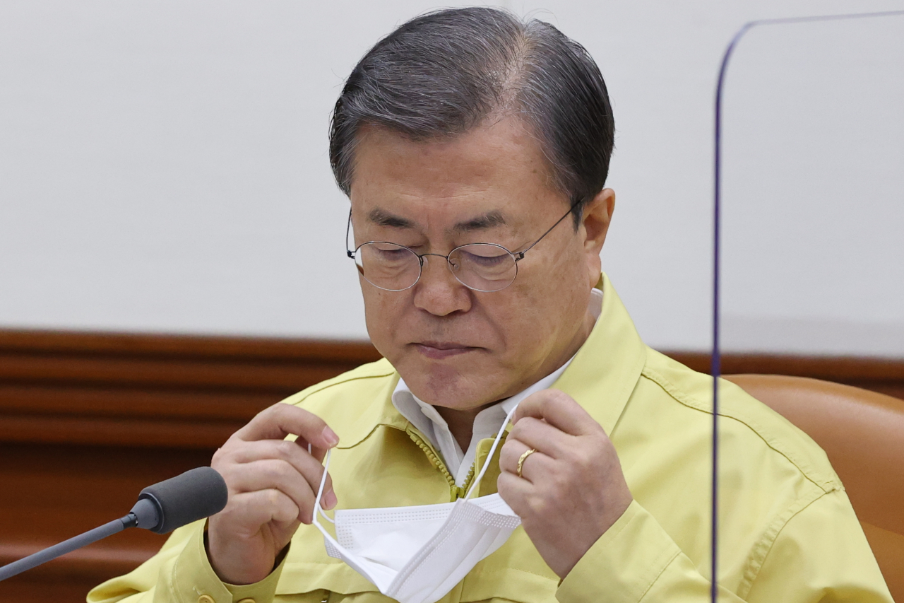 President Moon Jae-in takes off a mask before making opening remarks during an interagency meeting on virus response at the Central Disaster and Safety Countermeasure Headquarters in Seoul on Sunday. (Yonhap)