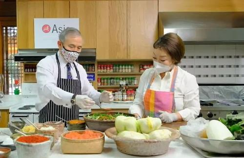 US Ambassador to South Korea Harry Harris (L) learns how to make kimchi with Chef Lee Hye-jung at the Habib House, his official residence in Seoul, on Tuesday. (Captured from the Facebook account of the Asia Korea Society Center)