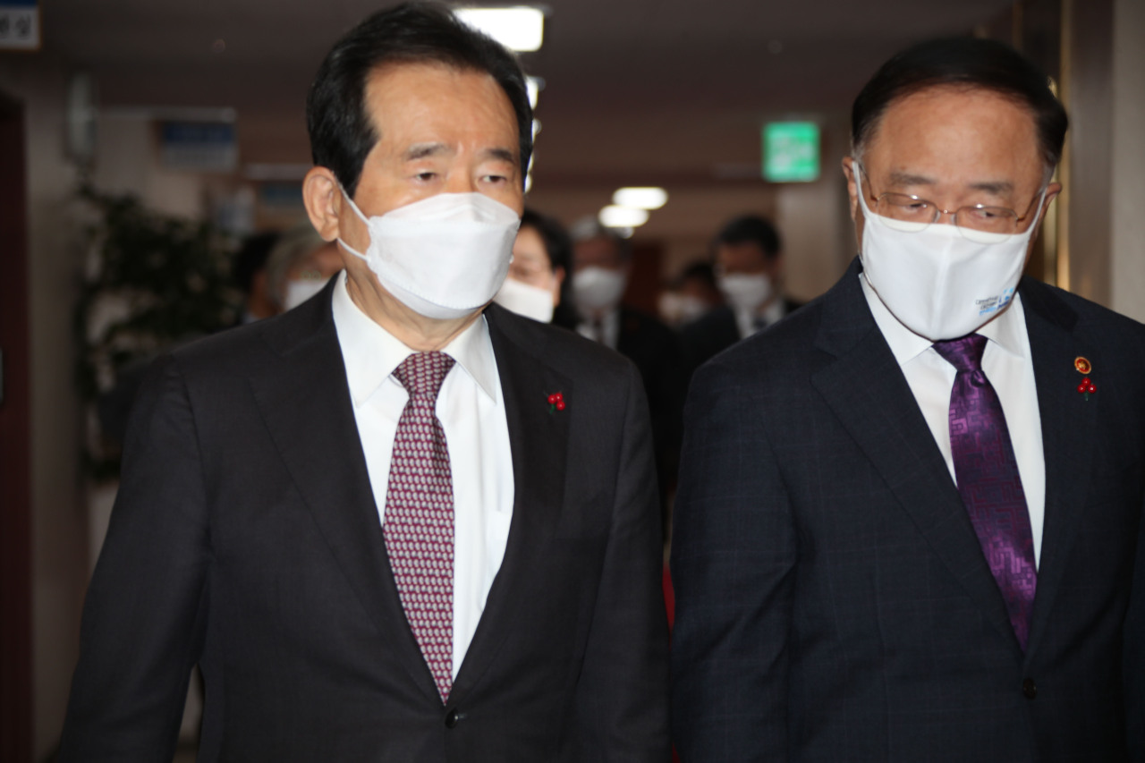 Prime Minister Chung Sye-kyun (L) and Finance Minister Hong Nam-ki arrive at a vaccine procurement-related government meeting held at the government complex in Seoul on Tuesday. (Yonhap)