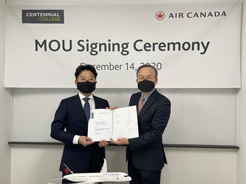 Bae Min-yuk (left) from Centennial College's Far East Asia Center and Lee Young from Air Canada pose for a picture after signing a memorandum of understanding to smooth the pathway to Canada for Korean students.