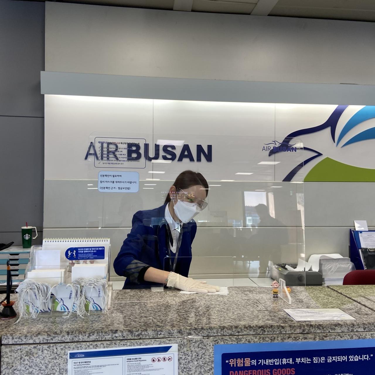 An Air Busan staff member cleans an airport check-in counter. (Air Busan)