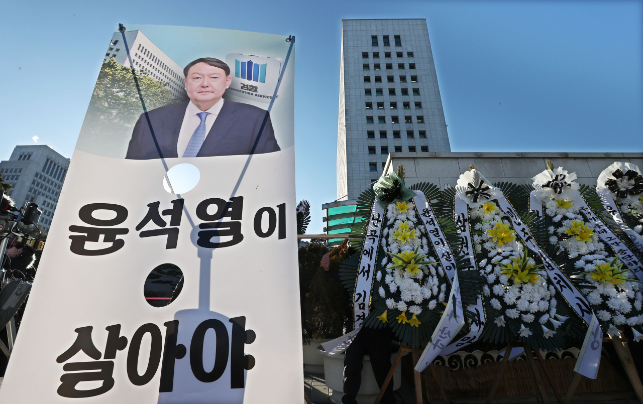 Signs and flowers are placed in front of the Supreme Prosecutors' Office in Seocho-gu, southern Seoul, on Thursday in support of Prosecutor General Yoon Seok-youl. With the two-month suspension under effect, the prosecution is under the leadership of acting Prosecutor General Cho Nam-kwan. (Yonhap)