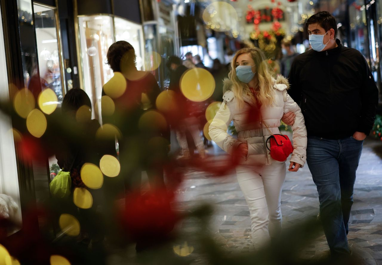 Shoppers, some wearing a face mask or covering due to the COVID-19 pandemic, look at shop window displays inside a christmas-themed Burlington Arcade in London on Saturday.  (AFP-Yonhap)