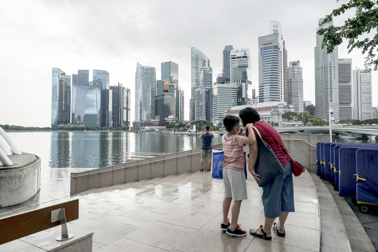 A family stands in front of the skyline of the financial district in Singapore on Dec. 8. (EPA-Yonhap)